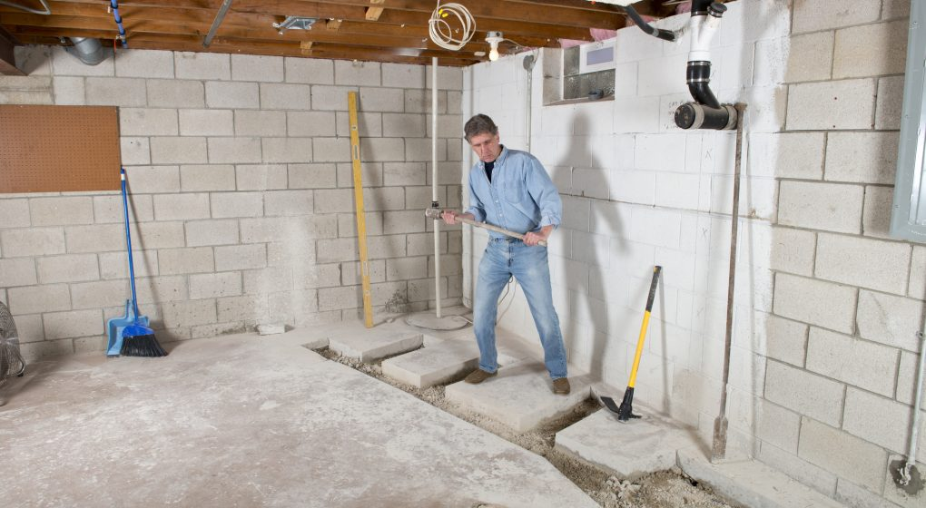 man in basement removing cement floor