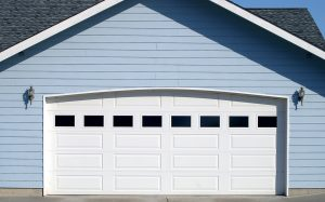 Arched garage door opening on new residence brightly lit up by the warm summer sun.